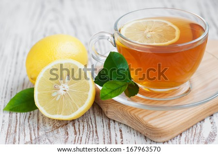 Tea cup  with lemon on a wooden table - stock photo
