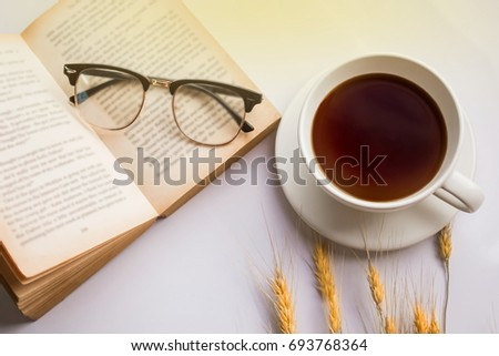 Tea cup with open books,eyeglasses and ear of Barley rice on white background.Copy space