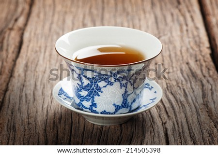 tea cup with tea leaf isolated on wooden plank - stock photo