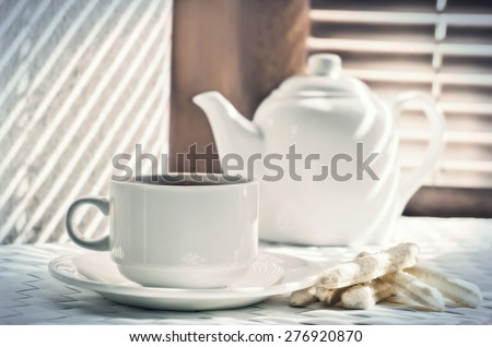 tea cup with teapot  against the background of blinds  - stock photo