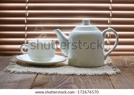 tea cup with teapot on old wooden table against the background of blinds - stock photo