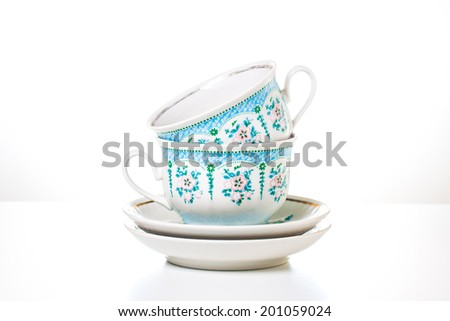 Tea cups and saucers on white background. Tea time. Porcelain dishes. Ornamental set for tea or coffee. Decorative background. - stock photo