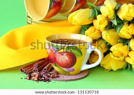 Tea cups and yellow tulips on green background - stock photo