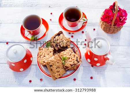 Tea cups top view. Tea time for party. Tea set red polka-dot, cookies on a wooden background. - stock photo