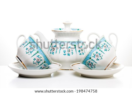 Tea cups with saucers and teapot on white background.Porcelain dishes.Ornamental tea set. Decorative background. Kitchenware. Tea time - stock photo
