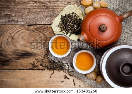 Tea cups with teapot on old wooden table. Top view. - stock photo