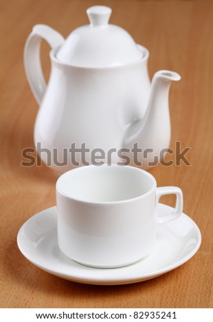 tea cups with teapot on table. - stock photo