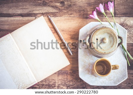 Tea cups with teapot with open book on old wooden table. Top view. - stock photo