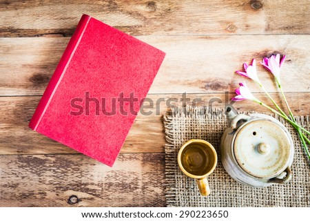 Tea cups with teapot with red book on old wooden table. Top view. - stock photo