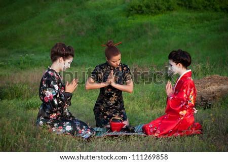 Tea drinking. Asian style portrait of three woman sitting on the grass and drinking tea - stock photo
