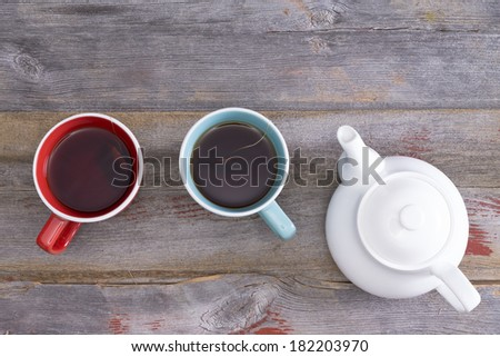 Tea for two with two ceramic cups of freshly brewed black tea standing on a weathered rustic wooden table alongside a teapot, overhead view with copy space - stock photo