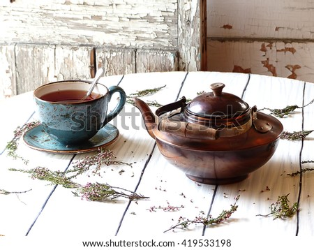tea from herbs, a heather, an old copper teapot, cup of tea,  selective focus - stock photo