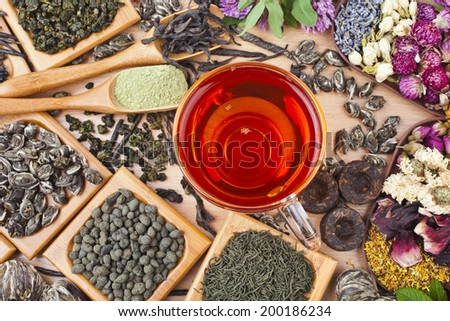 Tea glass cup and collection of different dry types tea (green,black, herbal) on kitchen wooden table background, top view surface - stock photo