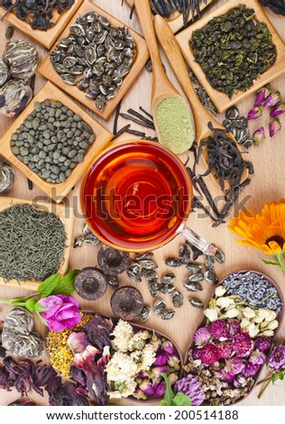 Tea glass cup and collection of different dry types tea (green,black, herbal) on kitchen wooden table background top view - stock photo