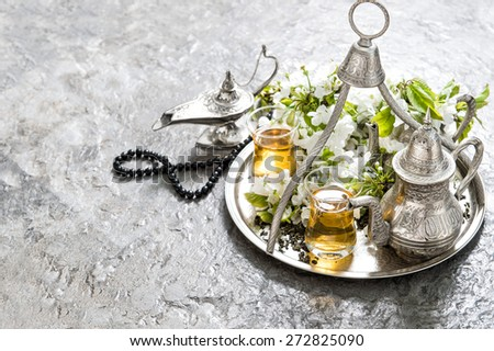Tea glasses and pot, arabian lantern and rosary. Islamic holidays decoration. Oriental hospitality concept - stock photo