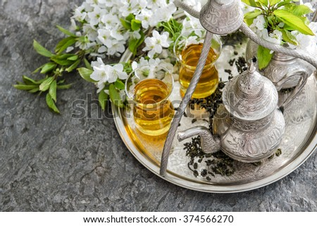 Tea glasses and pot, traditional sweets. Table setting with spring flowers - stock photo