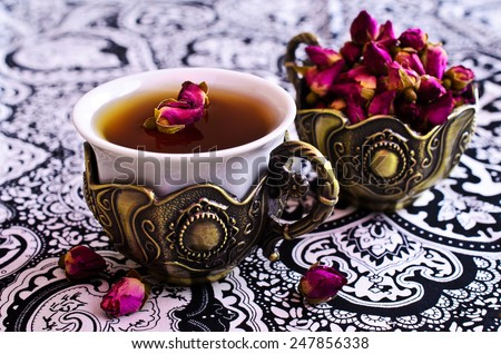 Tea in a beautiful metal Cup with Oriental motifs on the metal tray surrounded by dried rose buds - stock photo