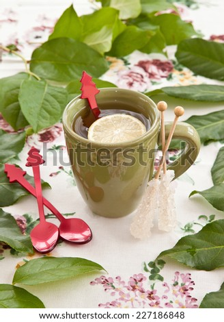 Tea in a green mug with a slice of lemon - stock photo