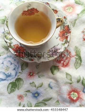 Tea in cup with matching saucer on flowery print cloth