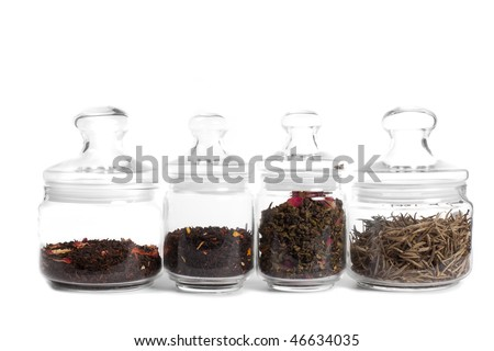 Tea in glass jars: (from left to right) milk puer, aromatized indian tea, oolong with rose, white tea (silver needles) isolated on white. - stock photo