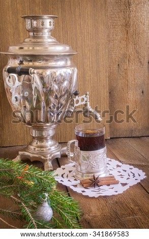 Tea in glass with coaster  and russian samovar on wooden background. Cinnamon and anise star with white doily. Home christmas decoration