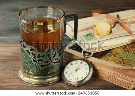 Tea in vintage glass-holder old book, letters  and watch on wooden table. retro filtered image - stock photo