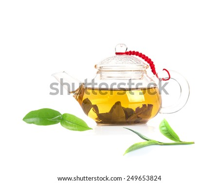 Tea is brewed in a transparent tea pot and green tea leaves - stock photo