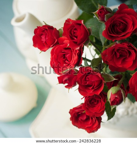 tea kettle and a bouquet of red roses