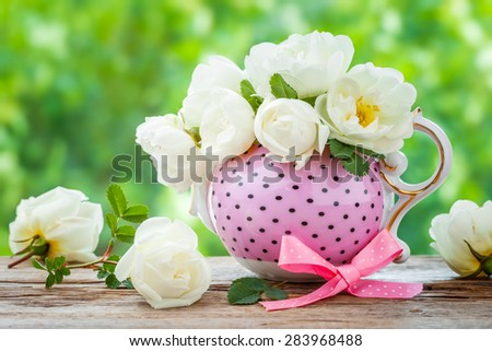 Tea kettle and bouquet of roses. Wedding or birthday still life. - stock photo