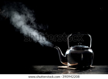 Tea kettle with boiling water on a black background - stock photo