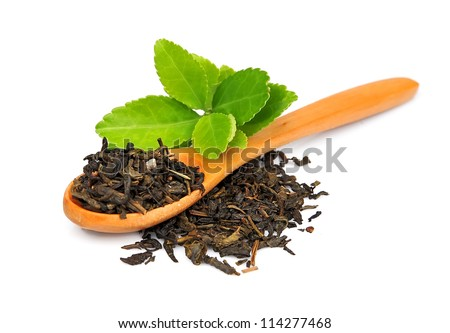 Tea leaves and dried tea  on a wooden spoon on white