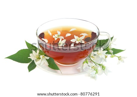 Tea leaves with fresh jasmine flowers and glass cup on white background - stock photo