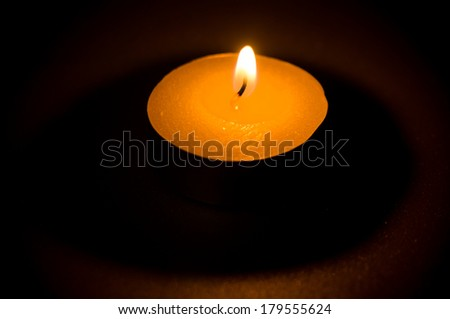 Tea light candle on black background