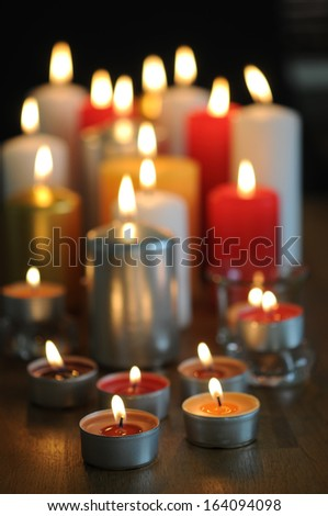 Tea lights and other beautiful candle burns with a beautiful candle flame - stock photo