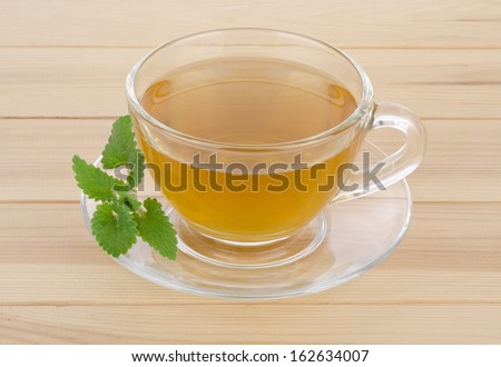 Tea mint in glass cup with mint leaves on wooden table background.