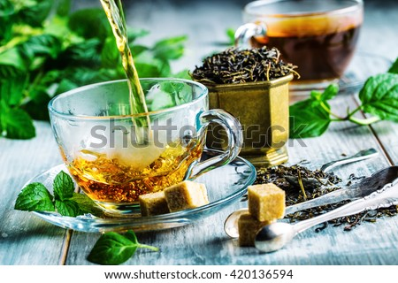 Tea. Mint Tea. Herbal tea. Mint leaf. Mint leaves. Tea in a glass cup, mint leaves, dried tea, sliced lime. herbs tea and mint leaves on a slate plate in a restaurant or teahouse tea room.