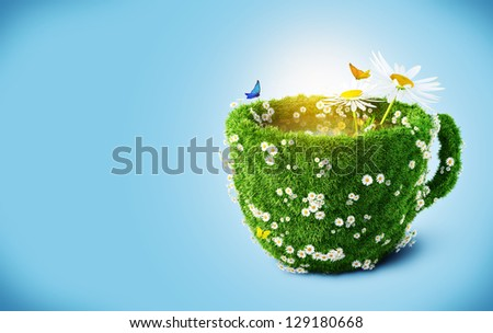 Tea mug from  grass and camomiles - stock photo