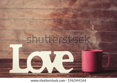 Tea or coffee cup with word Love on wooden table. - stock photo