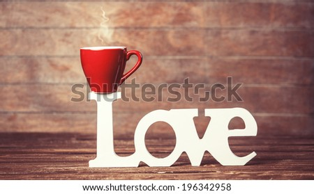 Tea or coffee cup with word Love on woodent table. - stock photo
