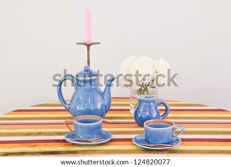 tea or coffee set on table with colorful line fabric in gray wall room