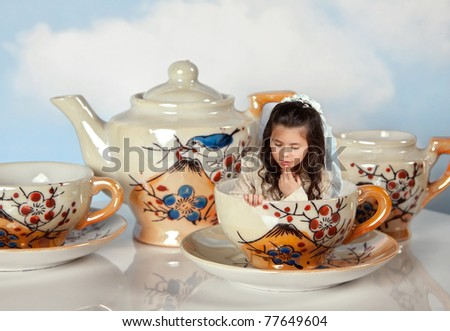 Tea party with antique tea cups and a miniature girl like in alice in wonderland - stock photo
