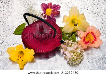 tea pot between the flowers on a rainy day