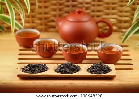 tea pot, four cups and tray with rolled tea leaves - stock photo