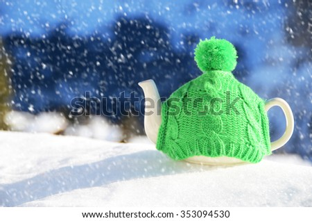 Tea pot in the knitted cap on the snow - stock photo