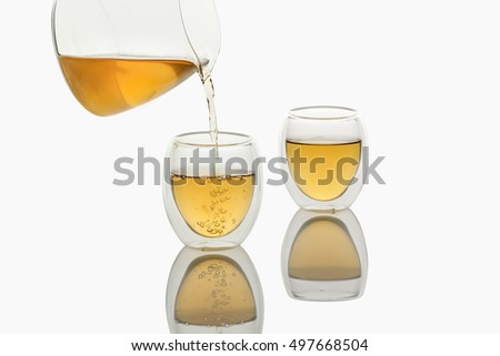 Tea pouring into Double-wall Glass Tea Cup, isolated in white