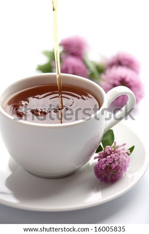 tea pouring into white cup isolated - stock photo