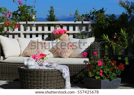 Tea-set and beautiful flowers on sunny terrace.