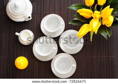 Tea set on a bamboo mat with yellow tulips and yellow candle in the form of eggs