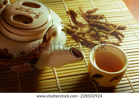 Tea set with leaves on bamboo mat,sepia color filtered. - stock photo