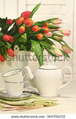 Tea set with tulip flowers for Easter - stock photo